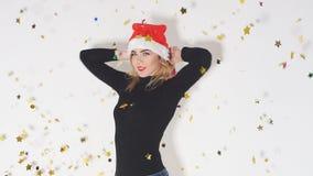 Жизнерадостная счастливая девушка в красной шляпе Санта Клаусе имея потеху пока танцующ под фейерверками confetti акции видеоматериалы