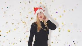 Жизнерадостная счастливая девушка в красной шляпе Санта Клаусе имея потеху пока танцующ под фейерверками confetti видеоматериал