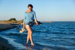 Жизнерадостная темн-с волосами женщина в покрашенной куртке потока и джинсовой ткани усмехается, идется вдоль пляжа и наслаждаетс стоковое изображение