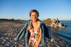 Жизнерадостная темн-с волосами женщина в покрашенной куртке потока и джинсовой ткани усмехается, идется вдоль пляжа и наслаждаетс стоковые изображения