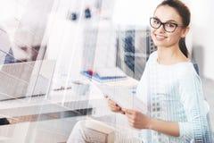 Жизнерадостная усмехаясь женщина стоя в офисе стоковое изображение rf