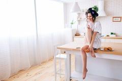 Жизнерадостная халатная молодая женщина с curlers в haor Сидеть на таблице в кухне и смеяться Чашка владением в руке Телефон стоковое фото rf