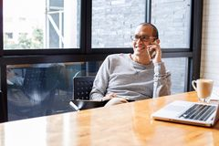 Жизнерадостное азиатское мужское предприниматель мелкого бизнеса говоря на телефоне с клиентом пока сидящ в офисе скопируйте косм стоковое изображение