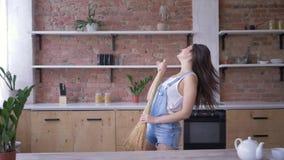 Жизнерадостное домашнее хозяйство, смешная женщина домохозяйки поет в венике как микрофон во время домашнего хозяйства акции видеоматериалы