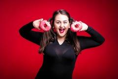 Жизнерадостное тучное брюнет имеет потеху представляя с очень вкусными donuts добавочно Стоковая Фотография RF