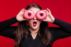 Жизнерадостное тучное брюнет имеет потеху представляя с очень вкусными donuts добавочно Стоковая Фотография