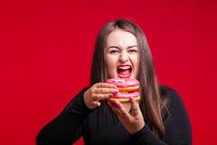 Жизнерадостное тучное брюнет имеет потеху представляя с очень вкусными donuts добавочно Стоковое Изображение