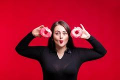 Жизнерадостное тучное брюнет имеет потеху представляя с очень вкусными donuts добавочно Стоковые Изображения