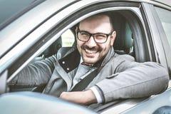 Жизнерадостно молодой человек в автомобиле стоковое изображение