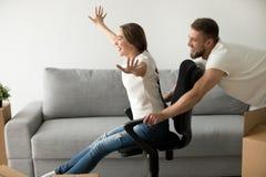 Жизнерадостные беспечальные пары имея потеху играя при стул двигая внутри Стоковые Фотографии RF