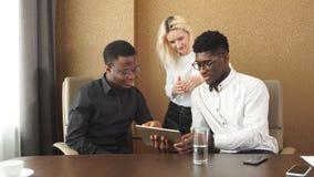 Жизнерадостные бизнесмены используя цифровой планшет пока сидящ на столе сток-видео