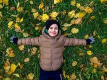 Жизнерадостные 4 года старого мальчика лежа на желтом цвете выходят в осень Взгляд сверху Стоковое Фото