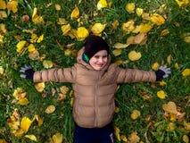 Жизнерадостные 4 года старого мальчика лежа на желтом цвете выходят в осень Взгляд сверху Стоковые Изображения