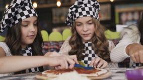 Жизнерадостные девушки в форме варя пиццу, на мастерском классе вождя в кафе видеоматериал