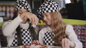 Жизнерадостные девушки в форме варя пиццу на мастерском классе вождя в кафе 4K акции видеоматериалы