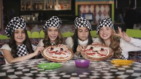 Жизнерадостные девушки в форме имея потеху на мастерском классе вождя в кафе сток-видео