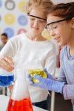 Жизнерадостные девушки смешивая химикаты в большой склянке Стоковая Фотография RF