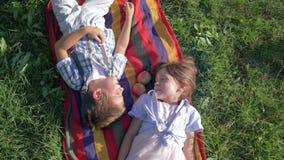 Жизнерадостные дети на смехе природы и лежать на шотландке с яблоками на зеленой траве сток-видео