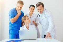 Жизнерадостные доктора используя компьтер-книжку совместно на работе Стоковые Фотографии RF