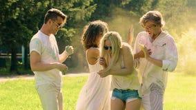 Жизнерадостные друзья бросая краску на один другого, фестиваль порошка Holi, наслаждение видеоматериал