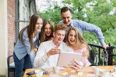 Жизнерадостные друзья возбужденные о новой таблетке на предпосылке кафа Концепция соединения и технологии Стоковые Фото