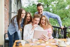 Жизнерадостные друзья возбужденные о новой таблетке на предпосылке кафа Концепция соединения и технологии Стоковые Фотографии RF