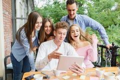 Жизнерадостные друзья возбужденные о новой таблетке на предпосылке кафа Концепция соединения и технологии Стоковая Фотография