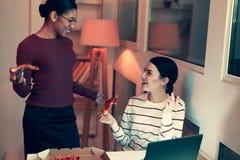 Жизнерадостные друзья говоря друг к другу пока ел пиццу Стоковые Фото