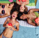 Жизнерадостные друзья лежа poolside с арбузом стоковое фото rf