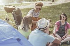 Жизнерадостные друзья организуя пикник с песней стоковое фото