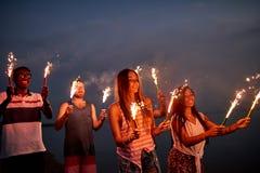 Жизнерадостные друзья с бенгальскими огнями на пляже лета стоковые изображения