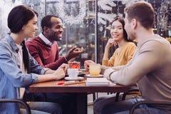 Жизнерадостные 4 друз беседуя совместно Стоковые Изображения RF