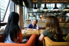 Жизнерадостные женщины сидя на уютном кофе кафа, усмехаться и выпивать Стоковое Фото