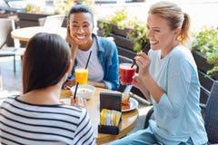 Жизнерадостные женщины слушая к их другу во время обеда Стоковое Фото