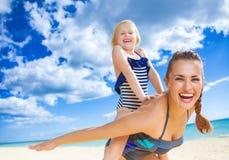 Жизнерадостные здоровые мать и ребенок на seashore имея время потехи стоковые фото