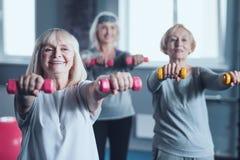 Жизнерадостные зрелые женщины используя гантели пока работающ на фитнес-клубе Стоковое фото RF