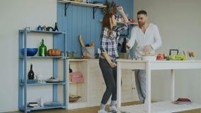 Жизнерадостные и привлекательные молодые пары в влюбленности танцуя совместно танец rocknroll в кухне дома на праздниках акции видеоматериалы