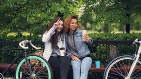Жизнерадостные кавказские и Афро-американские подруги принимают selfie делая усик от волос и представляя с акции видеоматериалы