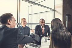 Жизнерадостные коллеги говоря во время работы в офисе Стоковые Фото