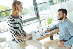 Жизнерадостные коллеги обсуждая работу в офисе стоковое фото rf