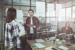 Жизнерадостные коллеги работают в офисе Стоковое Изображение RF