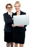 Жизнерадостные корпоративные повелительницы используя компьтер-книжку Стоковые Фото