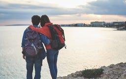 Жизнерадостные любящие пары смотря заход солнца около моря Стоковые Фото