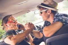 Жизнерадостные модные парни сидя в автомобиле и подготавливая для путешествия лета стоковые изображения rf
