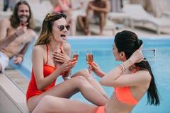 жизнерадостные молодые женщины в вине и смеяться swimwear выпивая стоковые изображения rf