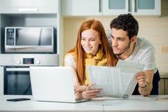 Жизнерадостные молодые пары высчитывая их счеты дома Стоковые Изображения RF