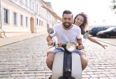 Жизнерадостные молодые пары ехать самокат и имея потеху Стоковые Изображения RF