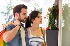Жизнерадостные молодые пары ходя по магазинам совместно и смотря окна магазина Стоковые Фото