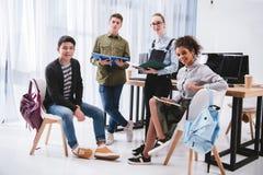 жизнерадостные молодые студенты с ученическими книгами и смотреть планшета стоковое фото rf