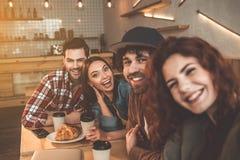 Жизнерадостные молодые человеки и женщины имея потеху в кафе Стоковое Изображение RF